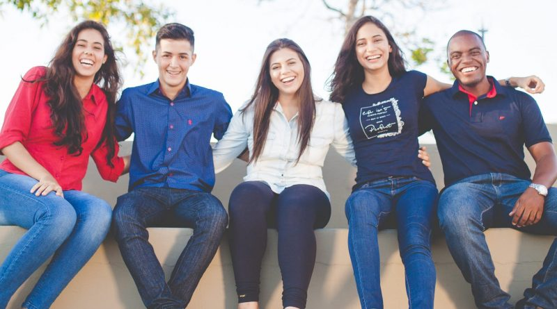 Een groep jongeren die op een rand bij een boom zitten