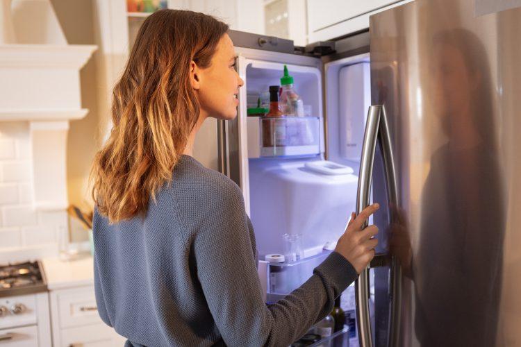 Vrouw opent de koelkast